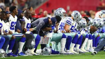 Dallas Cowboys players and owner Jerry Jones take a knee before national anthem