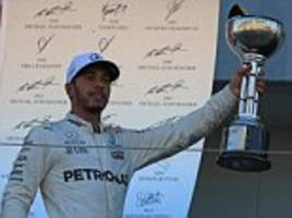 lewis hamilton has one hand on the f1 trophy