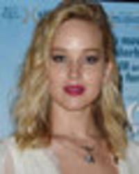 Jennifer Lawrence flashes ample cleavage in plunging lace gown