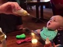 Dad squirts milk into his baby boy's mouth