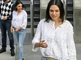 mila kunis flashes a bit of midriff in a sheer white top