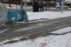 strong winds blow metal sign off store along busy main road