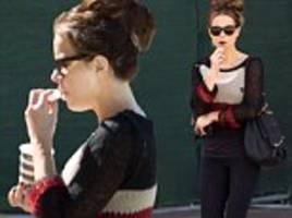 kate beckinsale nibbles a snack and carries a drink as she strolls