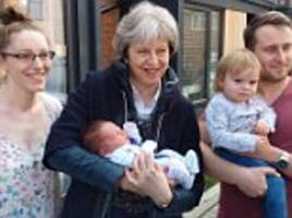 Theresa May cradles a new-born baby in Wokingham