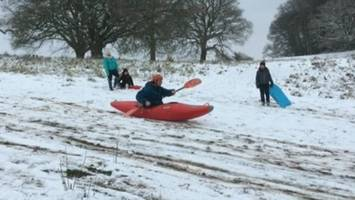 man uses kayak to sledge down hill in bristol