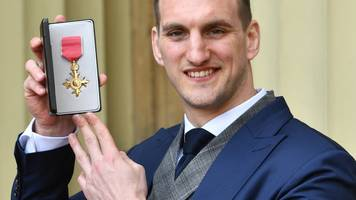 nice not to be wearing a towel for once - warburton collects obe from prince william