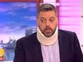 iain lee appears on gmb wearing a neck brace and looking pained... after he fell down a well