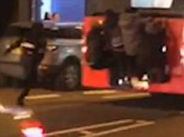 four people hang off the back of a london bus down brixton road