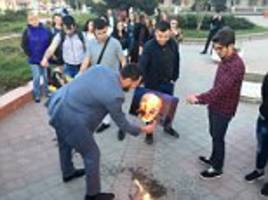 russians burn photos of trump, macron and theresa may