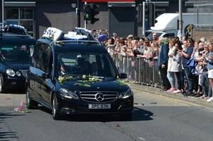 alfie evans funeral: tearful mourners applaud and toss flowers at hearse passing everton's goodison park stadium - with flowers spelling out warrior and our hero