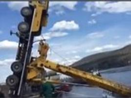 lift off! overloaded crane carrying a boat topples over in dramatic video