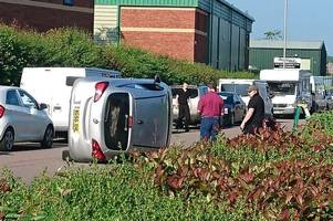 car flips onto side leaving road blocked on busy business estate