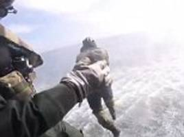 small unit of royal navy jump from helicopter during training exercise