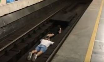 viral stunt: teenagers lay down on the tracks as subway train pulls in