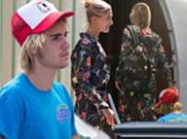 hailey baldwin rocks floral jumpsuit while leaving miami with fiance justin bieber as they board jet