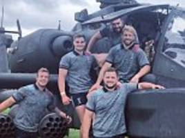 chris robshaw and harlequins team-mates pose for photo alongside an apache aircraft