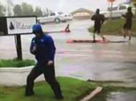 video shows journalist 'bravely' reporting on hurricane florence - until 2 men stroll casually past