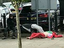 harrowing video shows spice 'zombies' slumped lifeless on town centre street as pedestrians walk by