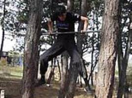 astonishing moment a bodybuilder hoists himself over a bar fixed between two trees