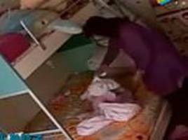 nanny is caught hitting and throwing a baby into bed before wrapping a towel around her head