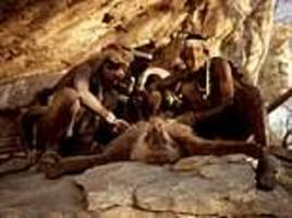 hunter-gatherers from tanzania butcher a dead baboon as they battle to preserve their way of life