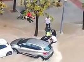 dramatic moment two women are dragged from beneath a car in raging flood waters in spain