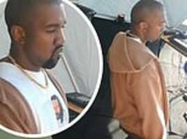 Kanye West rocks out to a local music in Uganda... where he's set to record his Yandhi album