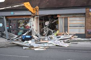 co-op wrecked in jcb ram raid on suburban street as bystander watches in disbelief