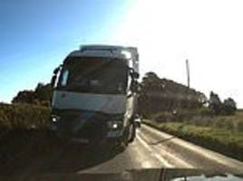 bmw driver rounds a corner to find a truck on the wrong side of road and swerves to avoid collision