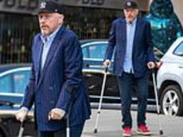 boris becker cuts a casual figure as he hobbles on crutches with bold red trainers for london outing
