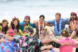prince harry and meghan markle share group hug with twins from cornwall on beach in australia