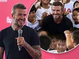 David Beckham looks happy as he joins aspiring footballers in Bangkok after family trip to Australia