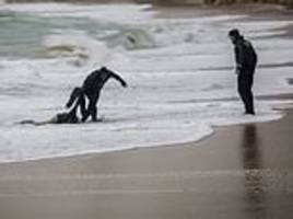 spanish coast guard clears body of mediterranean migrant victim from the beach