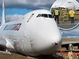 cargo plane skidded off runway, narrowly stopping short of the airport gate in wet and windy weather