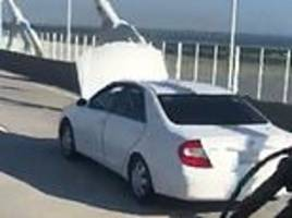 motorist spotted driving with car bonnet up over a busy road bridge