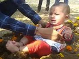 crying children are placed in cow dung by their parents