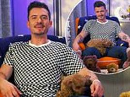 Orlando Bloom appears on CBeebies Bedtime Stories with pup Mighty sprawled out on his lap