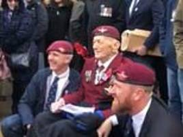 paratrooper in a wheelchair is helped to his feet by two younger veterans on armistice day