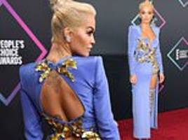 rita ora shows off her quirky sense of style in a plunging blue gown with thigh-high split
