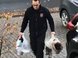 fed up father picks up his two-year-old daughter by the coat and carries her like a shopping bag