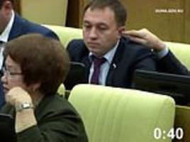 mp for vladimir putin's united russia party tickles colleague's ear during parliamentary session