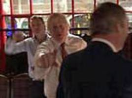 Former Foreign Secretary Boris Johnson looks uneasy as he is snapped alongside Farage