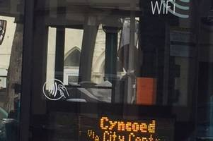 bus driver pictured reading newspaper at the wheel on busy city road