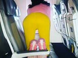 bizarre moment woman is filmed performing yoga onboard a united airlines plane to san diego
