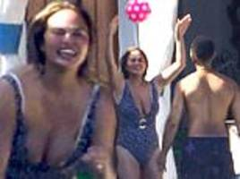 chrissy teigen sports patterned bathing suit while throwing a ball around with husband john legend