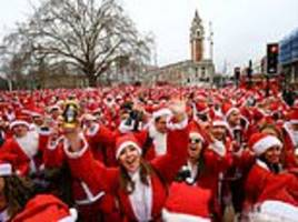 hundreds of revellers dress up as father christmas as they take part in annual santacon pub crawl