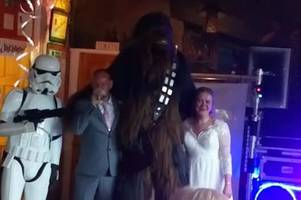 chewbacca and stormtrooper on dance floor at couple's star wars-themed wedding