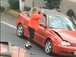 angry woman attacks vw golf convertible with a pole