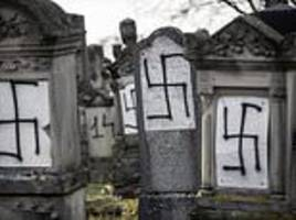 jewish tombstones desecrated with nazi swastikas in cemetery outside strasbourg