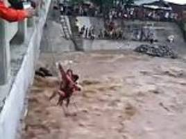 mother and her three children are dramatically winched to safety from a raging river